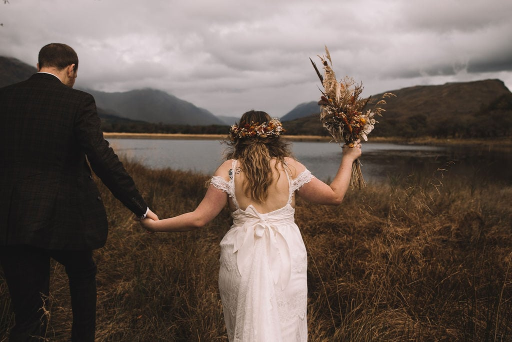 Bride and groom walking around a loch on the scotland elopement