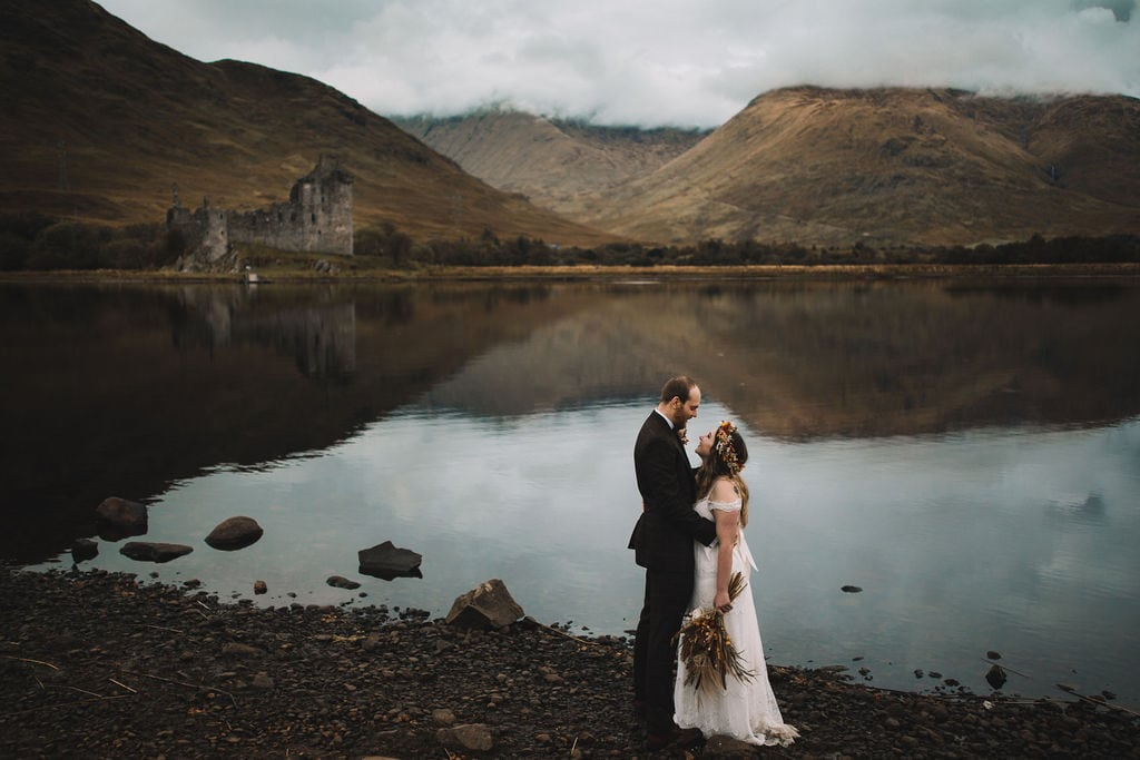 Scotland Elopement, couple cuddling in front of kilchurn castle on loch awe