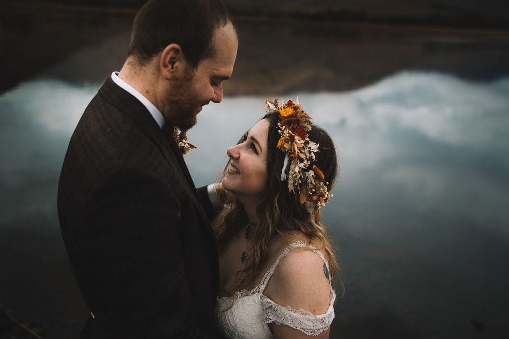 Scotland elopement. Bride and groom looking lovingly at each other with loch awe in the background