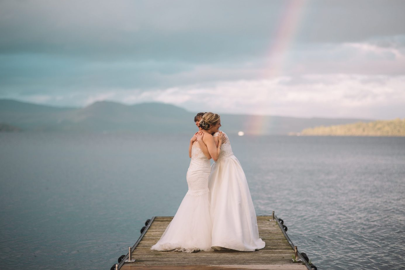 Scotland elopement. Bride and bride, same sex couple cuddling in front of loch lomond with rainbow, during an elopement
