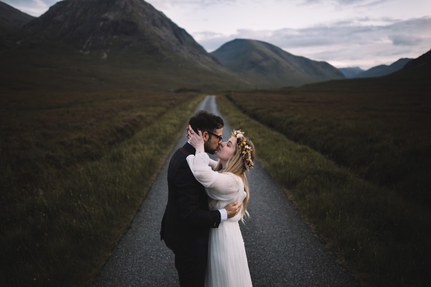 Scotland elopement. Couple kissing on the road to Glen Etvie at blue hour with the moon in the background.