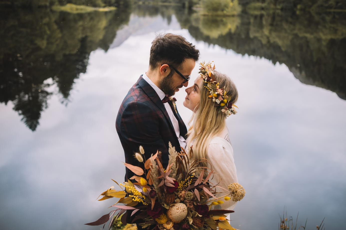 Bride and groom cuddling in front of lake with trees reflected in the background during their scotland  elopement