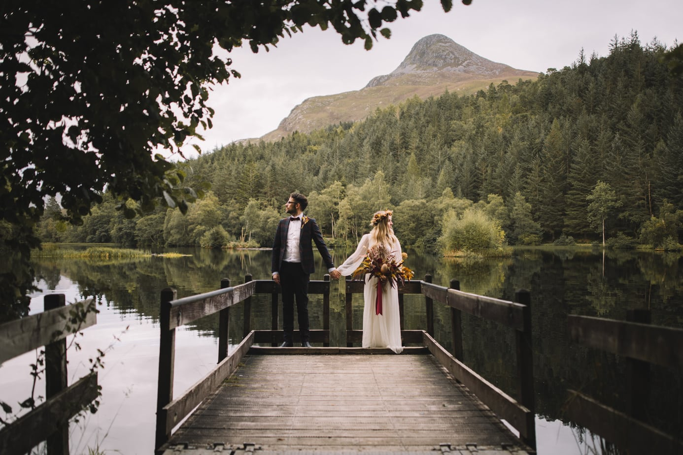 Couple holding hands in front of Glencoe lochan during their Scotland elopement
