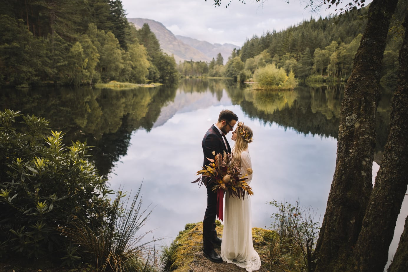 Glencoe lochan with a bride and groom stood gazing at each other. Bride is holding a bouquet of dried flowers.