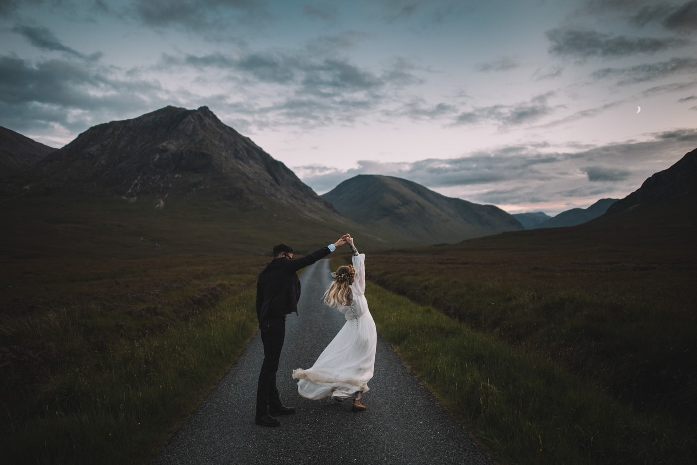 Set on the road to Glen Etive, A bride is twirling around her groom at blue hour and a little moon can be seen between the hills.