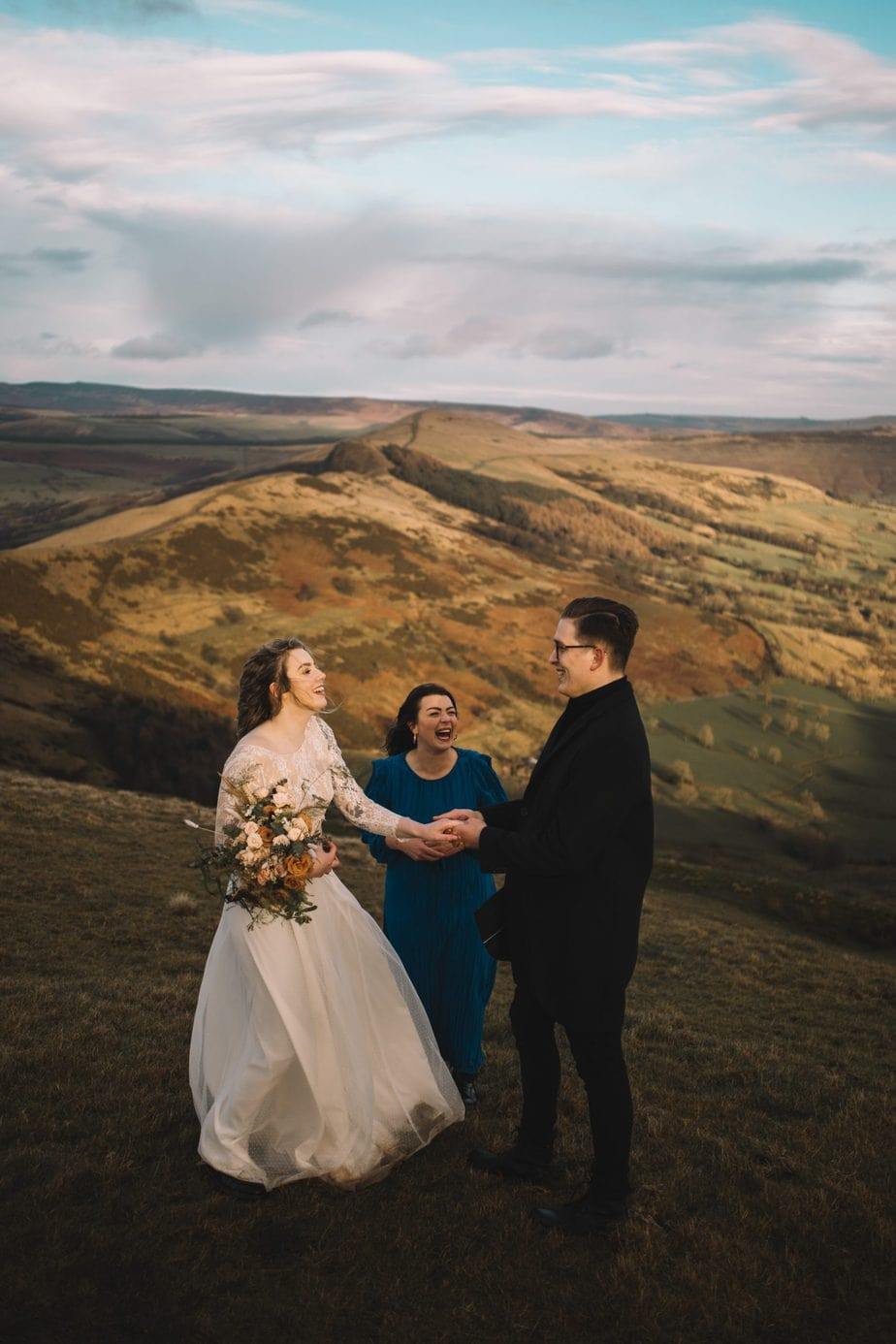 Couple laughing together with their celebrant during their elopement on Mam tor in the peak district.