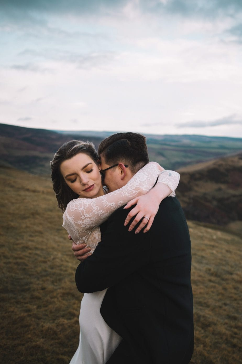 Bride and groom cuddling in the hills during their elopement.