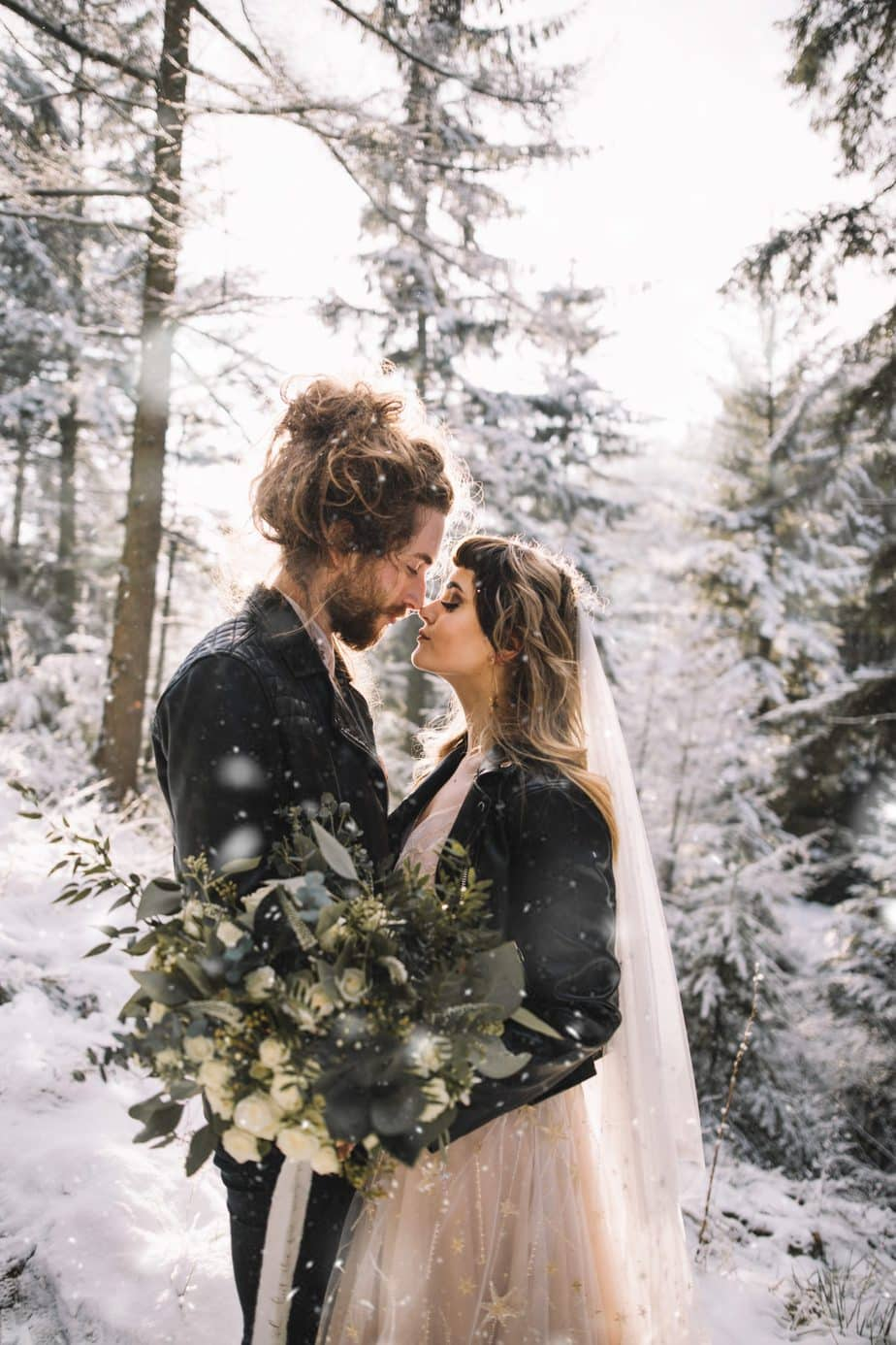 Couple touching noses in a snowy woodland with snow falling around them after they eloped. Bride wearing willowy celestial dress and holding a wild bouquet in green and white tones.