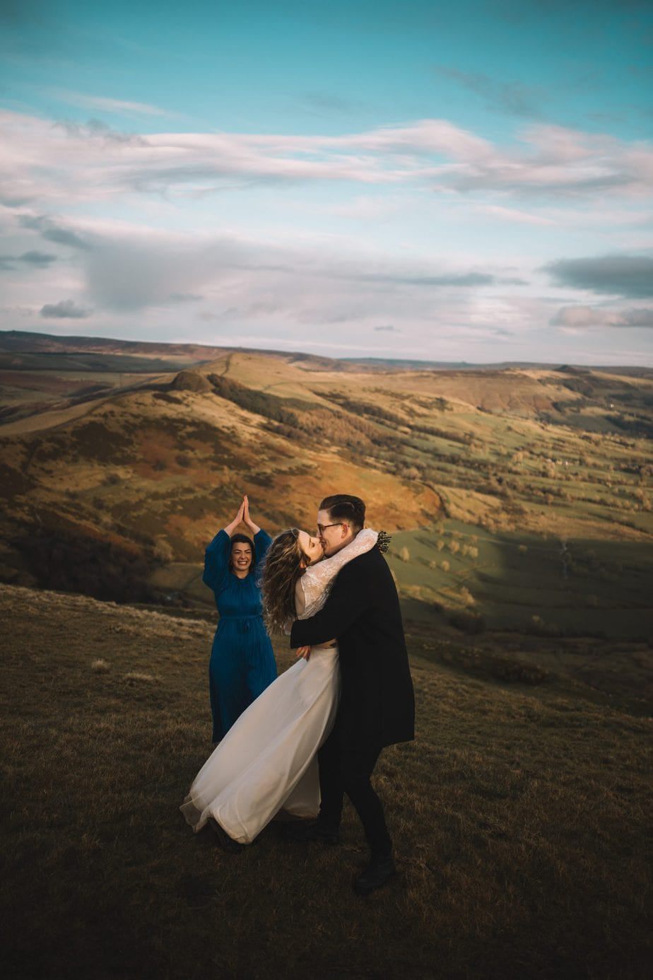 Bride and groom having their first kiss after an humanist elopement ceremony on Mam Tor in the peak district. Celebrant clapping and celebrating behind them.