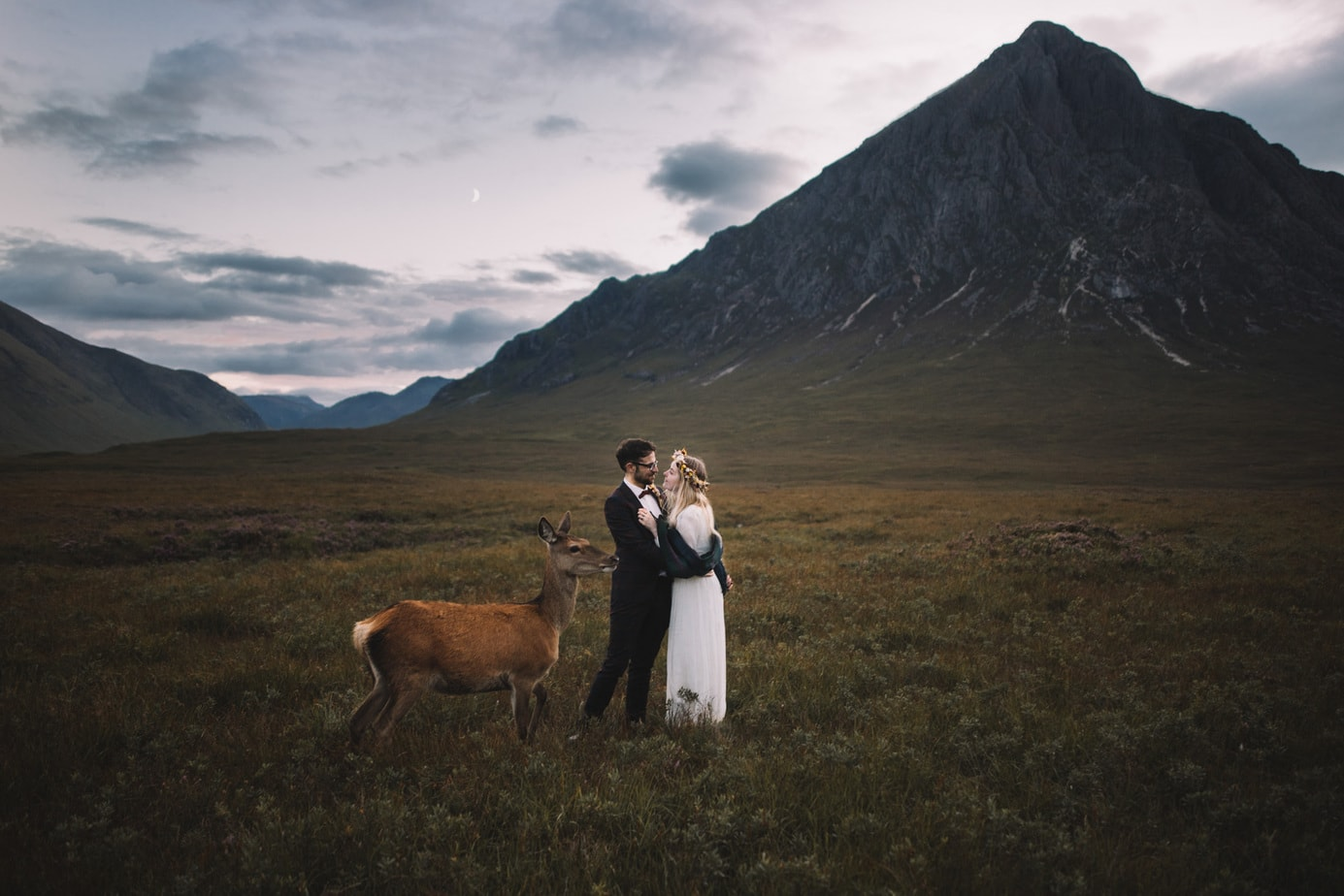 Scotland Elopement. Set in front of Glen Etive, a couple are cuddling during their elopement pictures while a deer is stood with them.