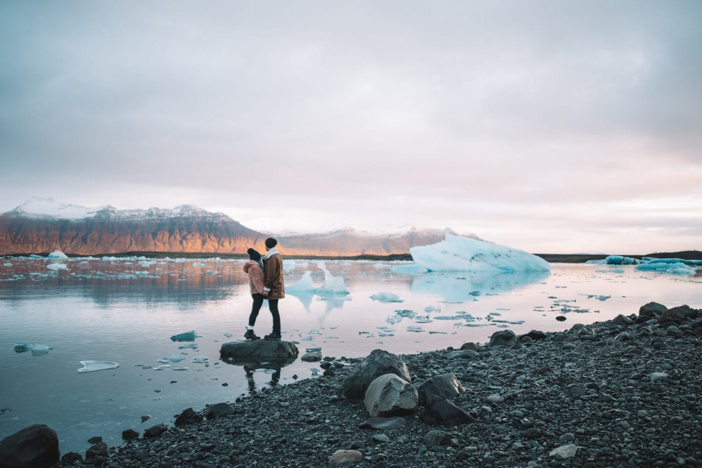 A couple standing in the Glacier Lagoon in Iceland.