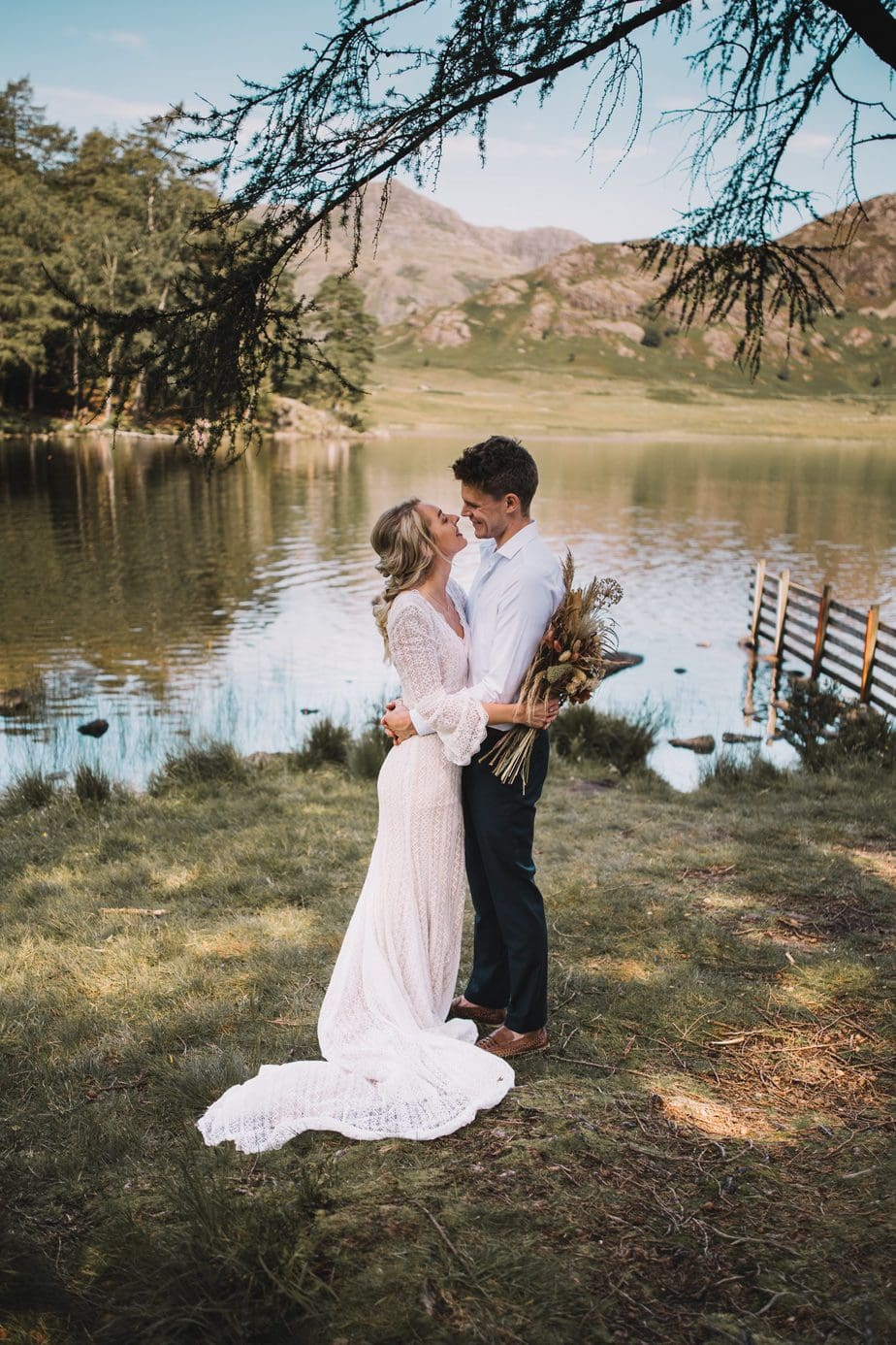 Couple cuddling with Blea Tarn lake in the background. During the Lake District elopement