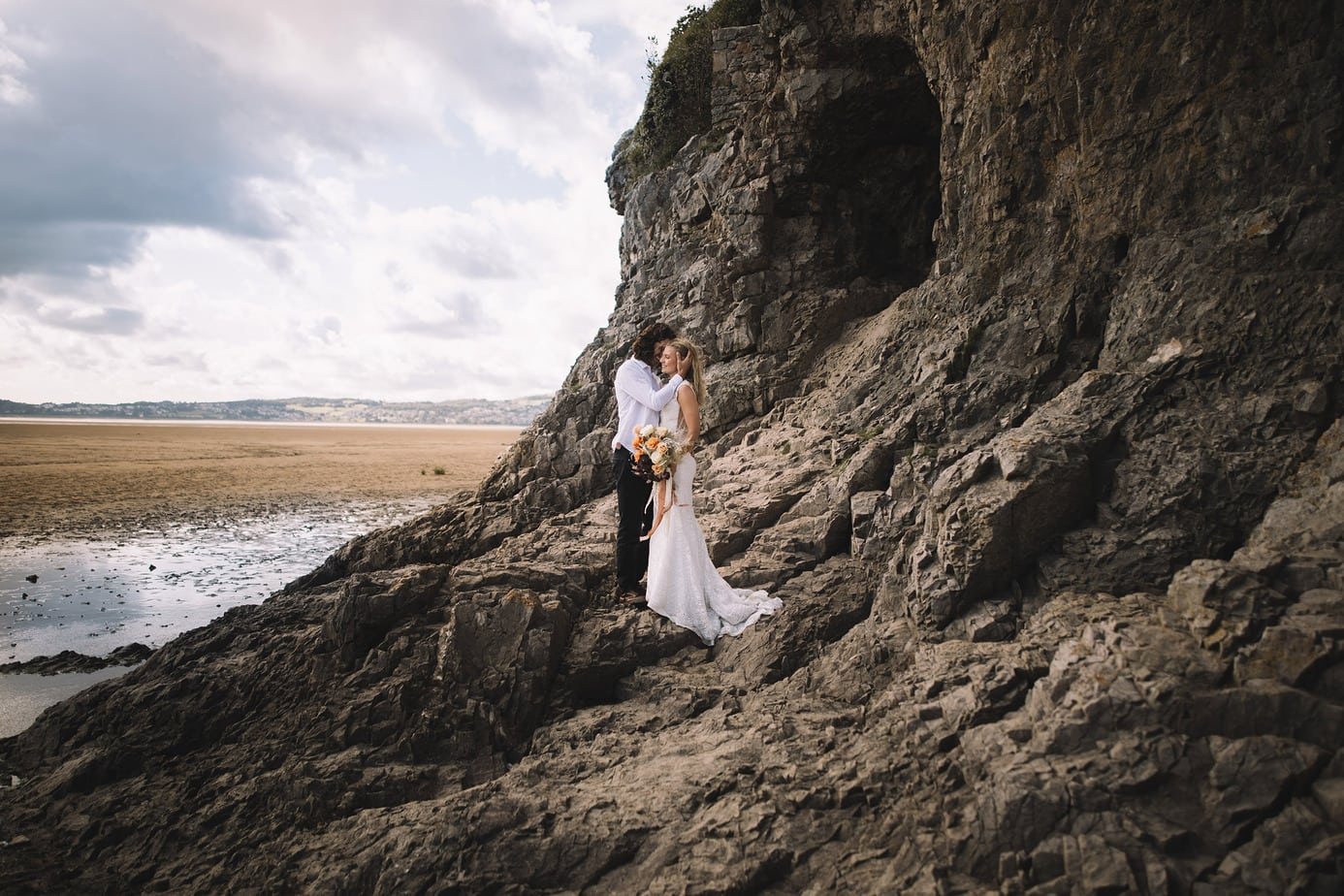 A couple standing on rocks with a cave behind them. On a beach on the Lake District, during their elopement.