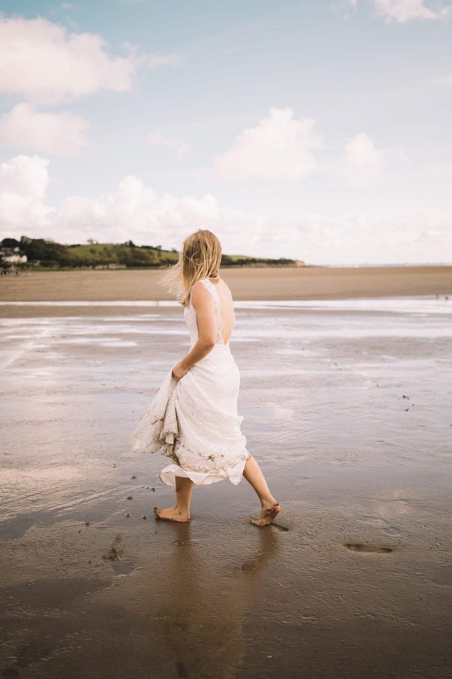 Bride walking barefoot on the beach